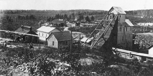First producer in Kirkland Lake, the Tough Oakes Mine. Mine buildings and miners' homes scattered across the rocky terrain. (Museum of Northern History)